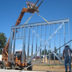 light gauge steel steel wall panel being hoisted into place by a construction crew