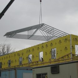 light gauge steel trusses and architectural framing being hoisted into place by a crane