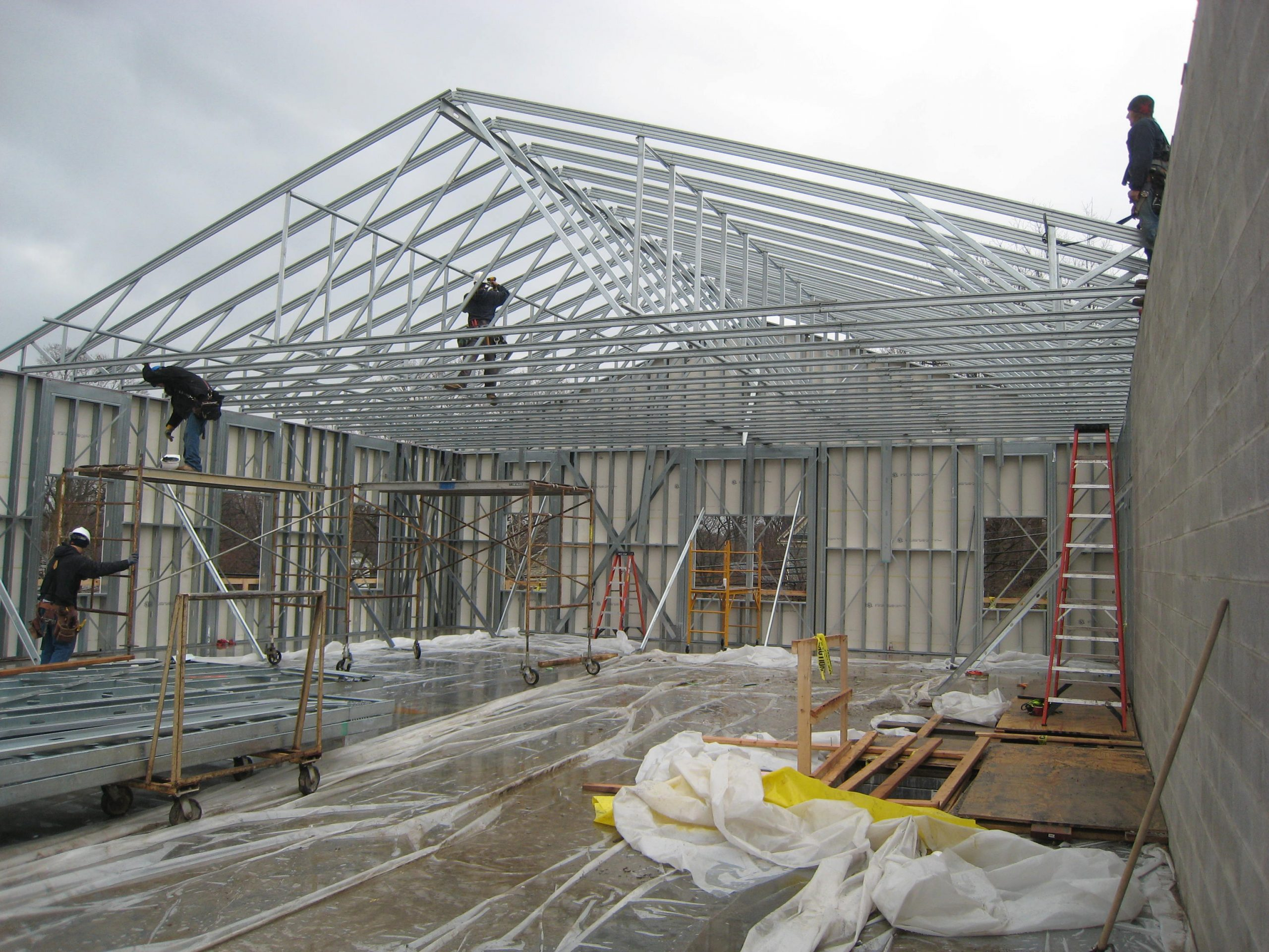 light gauge steel trusses and architectural framing being assembled by a construction crew